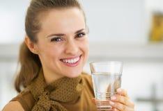 Stående av lyckligt dricksvatten för ung kvinna i kök Royaltyfria Bilder