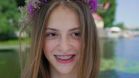 Stående av lyckligt kvinnligt tonårigt med hänglsen på tänder som ler på kameran 4K arkivfilmer