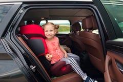 Stående av lyckligt sitta för flicka för litet barn som är bekvämt i bil s royaltyfri fotografi