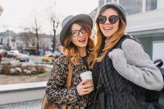 Stående av lycksaliga flickor som ut tillsammans hänger i kall morgon och utanför poserar med koppen kaffe Fantastiskt barn royaltyfri bild