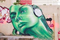 Stående av lyssnande musik för flicka i gröna grafitti Fotografering för Bildbyråer