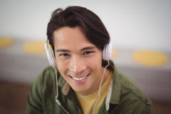 Stående av lyssnande musik för ung affärsman till och med hörlurar Royaltyfri Foto