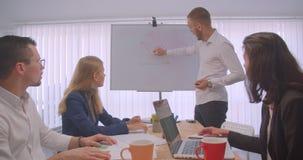 Stående av mötet för fyra collleagues i kontoret inomhus Affärsman som drar en graf på whiteboarden arkivfilmer