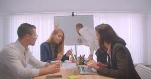 Stående av mötet och att ha för fyra collleagues en diskussion på arbetsplatsen inomhus Affärsman som drar en graf på stock video