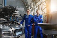 Stående av manliga mekaniker nära bilen i servicemitt royaltyfri bild