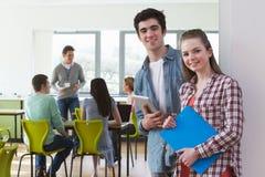 Stående av manliga och kvinnliga högskolestudenter i klassrum arkivfoto