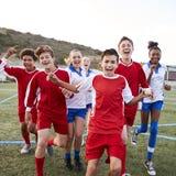 Stående av manligt och kvinnligt fira för högstadiumfotbolllag royaltyfri bild