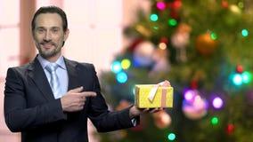 Stående av mannen i dräkt som pekar på gåvaasken lager videofilmer