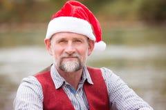Stående av mannen i hans 50-tal med jultomtenhatten Royaltyfria Bilder