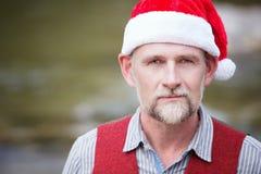 Stående av mannen i hans 50-tal med jultomtenhatten Arkivfoto