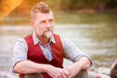Stående av mannen i hans 50-tal som sitter vid floden Royaltyfri Fotografi