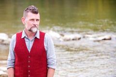 Stående av mannen i hans 50-tal som står vid floden Royaltyfri Bild