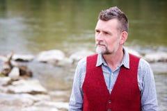 Stående av mannen i hans 50-tal som står vid floden Arkivbilder