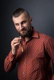 Stående av mannen med den hållande cigarren för svans Royaltyfria Bilder