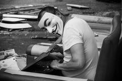 Stående av mannen med fejdmaskeringen och coumputer i övergiven fabrik på tappningfåtöljen royaltyfri foto