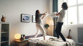 Stående av mannen och kvinnan som har gyckel med kuddekampen som kysser därefter i säng arkivfilmer