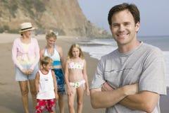 Stående av mannen på stranden med familjen arkivbilder