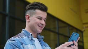 Stående av mannen som använder affärsappen på den smarta telefonen som går i stad Stilig ung man som meddelar på smartphonen stock video