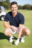 Stående av mannen som förlägger golfboll på utslagsplats arkivfoton