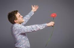 Stående av mannen som rymmer den röda blomman Royaltyfri Bild