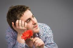 Stående av mannen som rymmer den röda blomman Arkivfoto