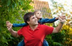 Stående av mannen som spelar med dottern som placeras på hans skuldror Arkivfoto