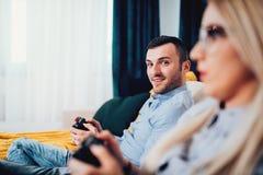 Stående av mannen som spelar videospel med den blonda frun Arkivfoto