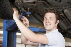 Stående av mekanikern Working On Wheel under bilen royaltyfri foto