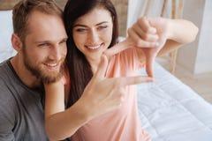 Stående av millennial par som inramar framsidor med händer Arkivbilder