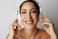 Stående av mode som ler den kalla flickan avriven till midjan i vit hörlurar som lyssnar till musik över tom vit Arkivbild