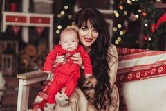 Stående av modern och den nyfödda sonen på bakgrund av den dekorerade julgranen med girlanden, bollar, röda bär Fotografering för Bildbyråer