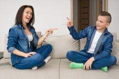 Stående av modern och hennes son på soffan hemma Arkivfoto