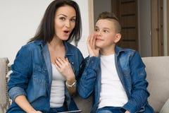 Stående av modern och hennes son på soffan hemma Royaltyfri Foto