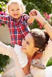 Stående av modern och sonen som utanför tillsammans spelar royaltyfri fotografi