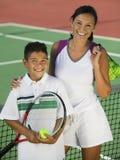 Stående av modern och sonen vid netto på tennisbanan Royaltyfria Foton