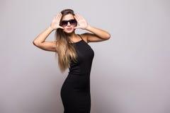 Stående av modeståenden av den unga härliga kvinnan i den svarta klänningen på grå färger arkivfoton
