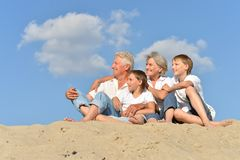 Stående av morföräldrar med deras barnbarn på sanden arkivbilder