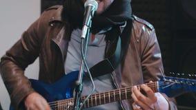 Stående av musikern som sjunger sång och spelar gitarren arkivfilmer