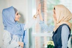 Stående av muslimkvinnan som ger höjdpunkt fem på kafét royaltyfria foton
