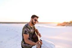 Stående av närbildståenden av den arabiska grabben som spelar gitarrstrin Royaltyfri Foto