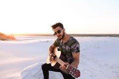 Stående av närbildståenden av den arabiska grabben som spelar gitarrstrin Royaltyfria Bilder