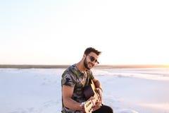 Stående av närbildståenden av den arabiska grabben som spelar gitarrstrin Fotografering för Bildbyråer