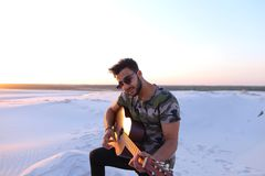 Stående av närbildståenden av den arabiska grabben som spelar gitarrstrin Arkivfoton