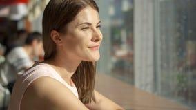 Stående av nätt drömlikt sammanträde för ung kvinna på tabellen i kafé nära att tänka för fönster Galleria för matdomstol arkivfilmer
