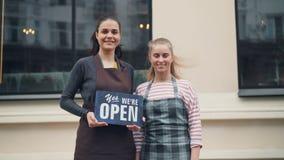 Stående av nätta unga kvinnor som rymmer det öppna tecknet som utomhus står nära det nya kafét lager videofilmer