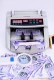Stående av ny indisk valuta, kassa som räknar maskinen och förstoringsglaset arkivfoto