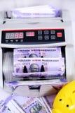Stående av ny indisk valuta, kassa som räknar maskinen och spargrisen arkivbilder