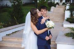 Stående av nygifta personer som går i parkera Bruden i bröllopsklänningen är kyssande hennes make på kinden, royaltyfri fotografi