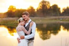 Stående av nyligen ett gift par Bröllopparet står på bakgrunden av beställningen arkivbilder