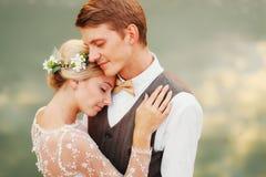 Stående av nyligen ett gift par Bröllopparet står på bakgrunden av beställningen Royaltyfri Foto
